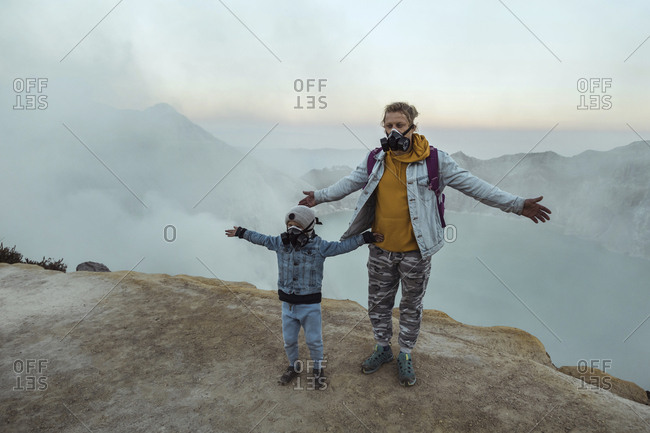 Father and son with respirator masks standing at the edge of volcano Ijen- Java- Indonesia