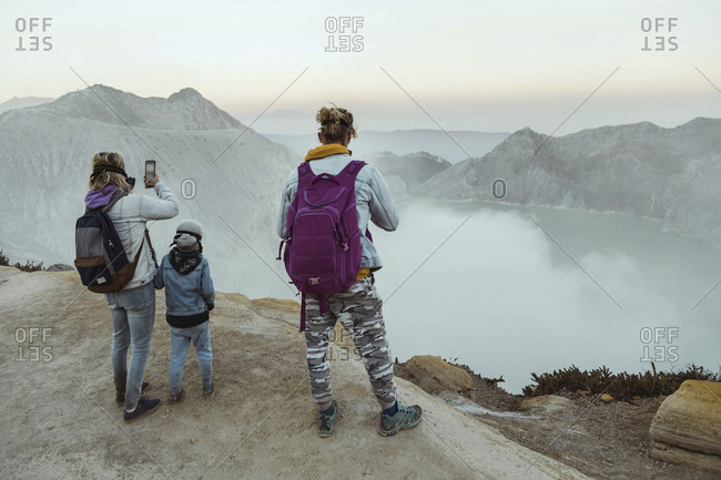 Family with respirator masks standing at the edge of volcano Ijen- Java- Indonesia