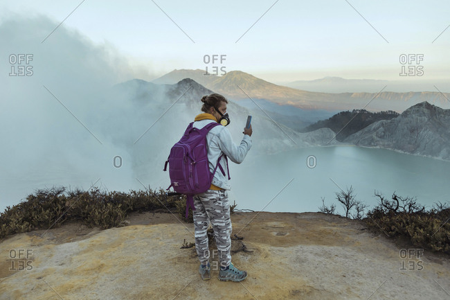 Man with respirator mask standing at the edge of volcano Ijen- Java- Indonesia