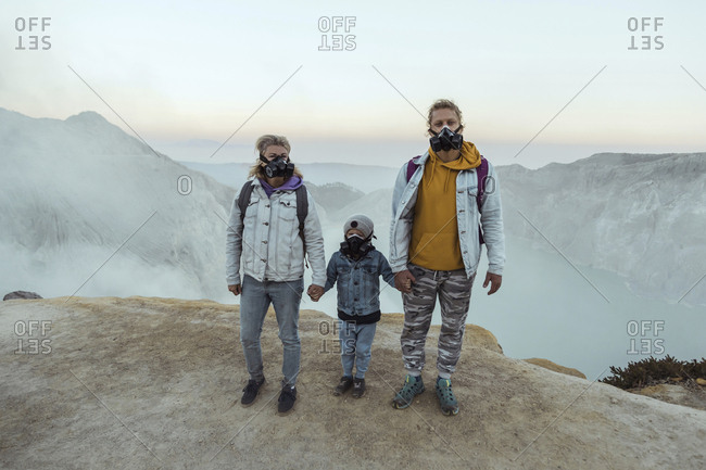 Family with respirator masks standing hand in hand at the edge of volcano Ijen- Java- Indonesia