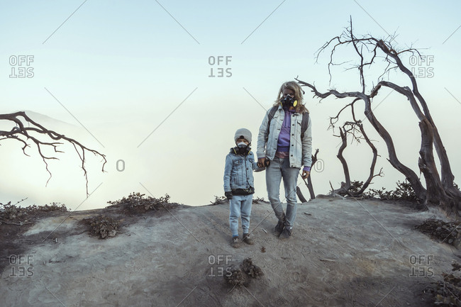 Mother and son with respirator masks standing hand in hand at the edge of volcano Ijen- Java- Indonesia