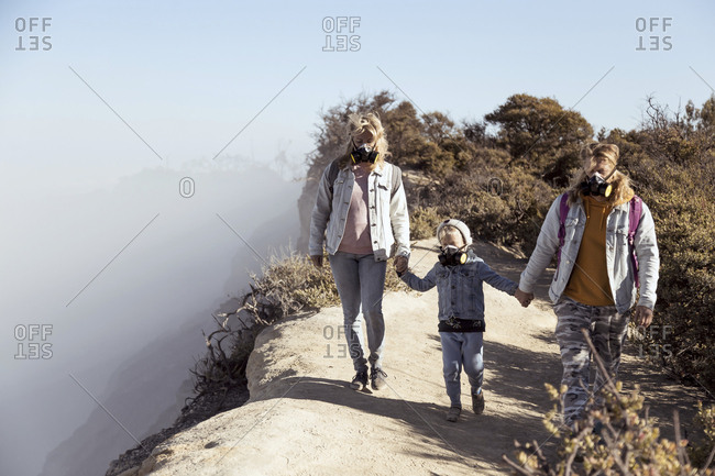 Family with respirator masks walking hand in hand along the edge of volcano Ijen- Java- Indonesia