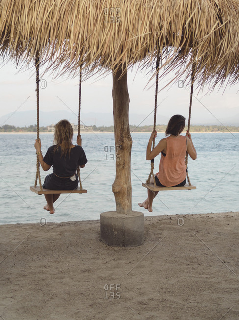 Back view of two women sitting on swings at seafront- Gili Islands- Bali