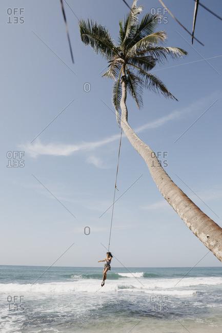 Full length of woman swinging from palm tree at beach against sky- Sri Lanka
