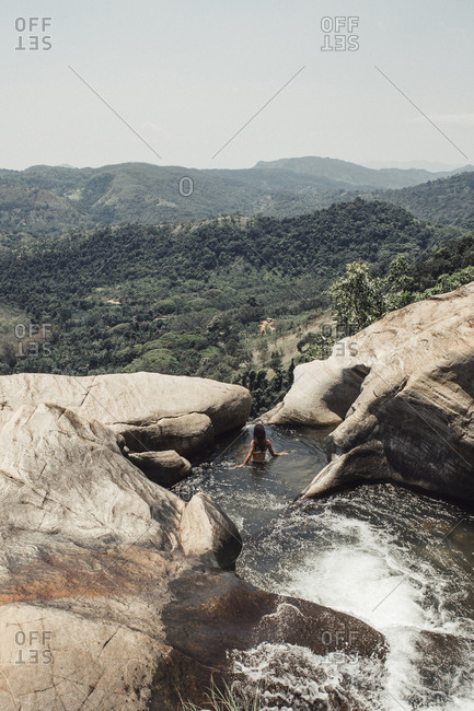 High angle view of young woman swimming in stream amidst rock formation at Sri Lanka