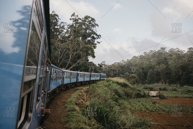 July 15, 2019: Train moving by agricultural field in Sri Lanka against sky