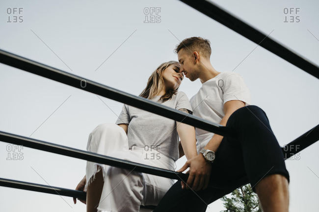 Young couple kissing each other on a climbing frame