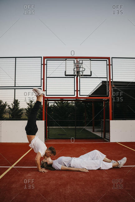 Young couple on a basketball ground- woman lying and man doing a handstand and kissing her