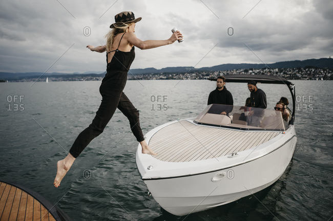 Young woman jumping on a boat on a lake