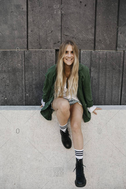 Portrait of smiling blond woman wearing green jacket sitting on a wall- Vienna- Austria