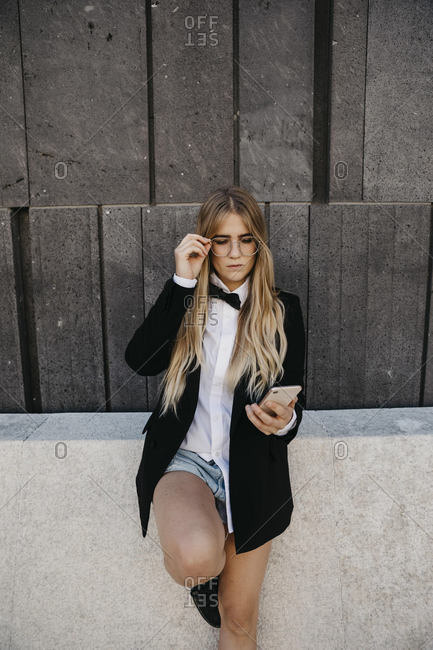 Portrait of blond young woman wearing black tie- and blazer looking at cell phone- Vienna- Austria