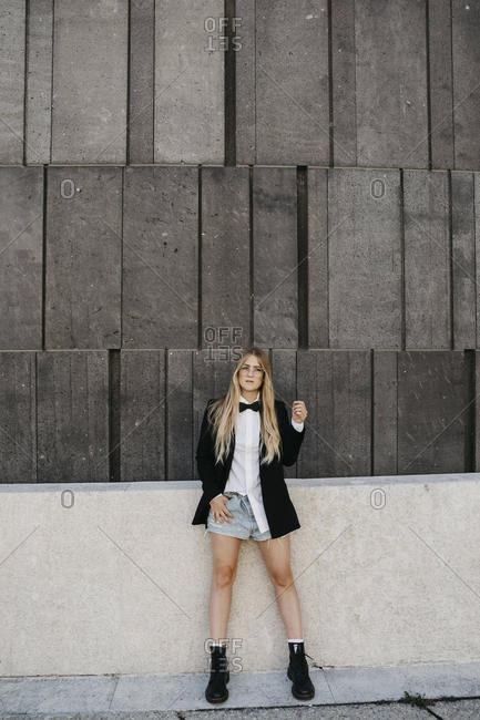 Portrait of blond young woman wearing black tie- blazer and jeans shorts- Vienna- Austria