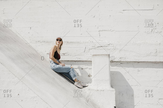 Young woman sitting in front of a white wall outdoors