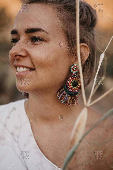 Portrait of smiling woman with earring and twigs- Joshua Tree National Park- California- USA