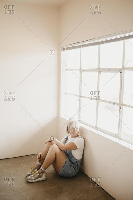 Smiling young woman sitting on the floor in a room