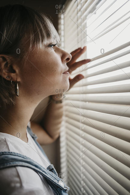 Young woman looking through blinds at the window