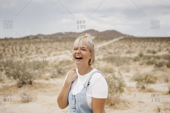 Portrait of laughing young woman in desert landscape- Joshua Tree National Park- California- USA