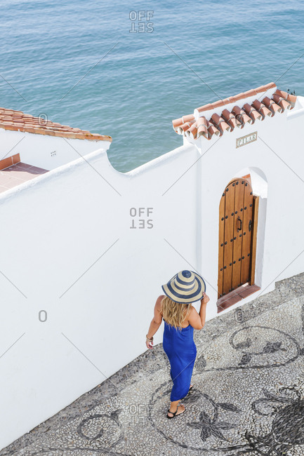 Back view of woman wearing blue dress and straw hat walking along alley- Nerja- Spain