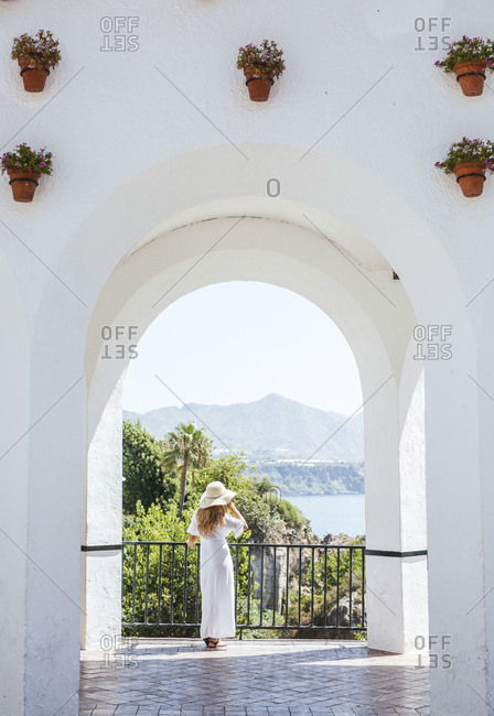 Back view of woman wearing white dress and straw hat looking at view- Nerja- Spain