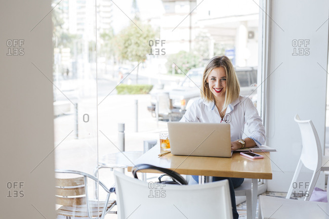 Portrait of smiling young woman with laptop on table in a cafe