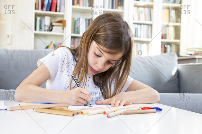 Portrait of girl drawing with colored pencil at home