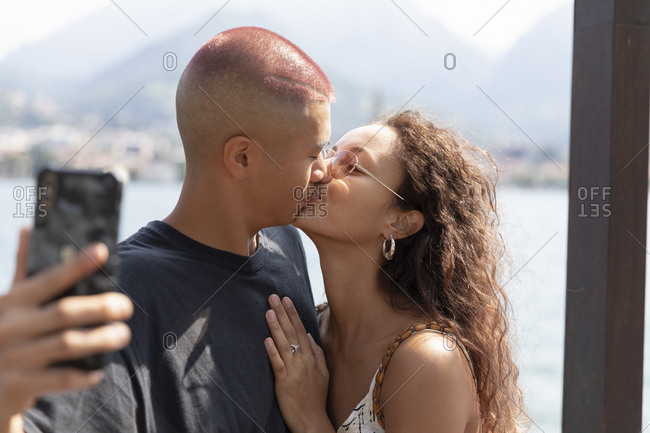 Young couple taking selfie with cell phone while kissing- Lecco- Italy