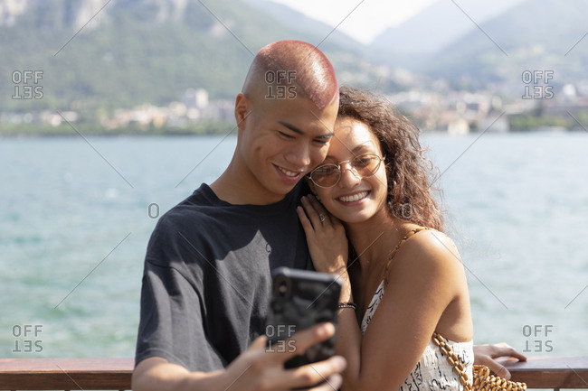 Portrait of happy young couple taking selfie in front of Lake Como- Lecco- Italy