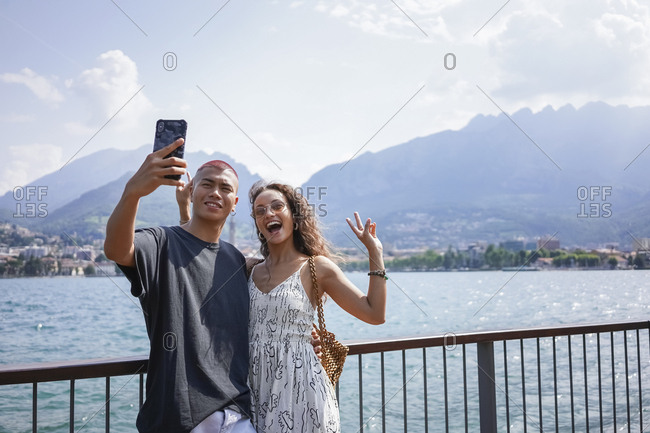 Portrait of young couple taking selfie in front of Lake Como- Lecco- Italy