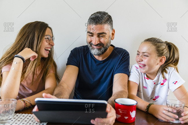 Happy father with two daughters using tablet at home