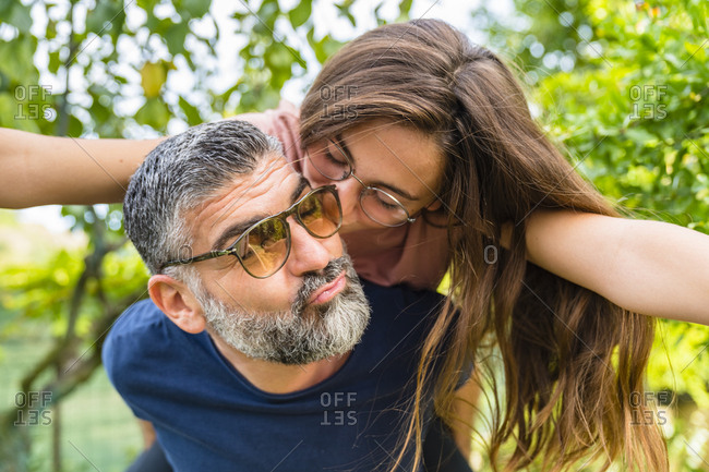 Father carrying daughter piggyback in garden