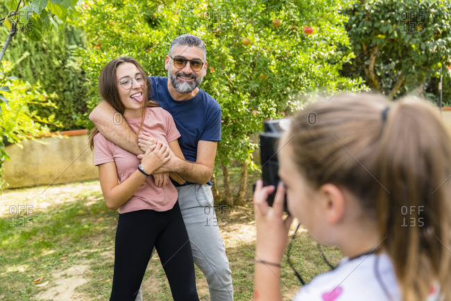 Girl taking a picture of happy father with daughter in garden
