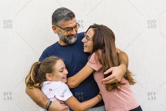 Father hugging two daughters outdoors