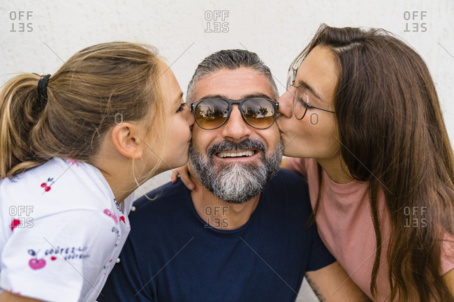 Two daughters kissing happy father