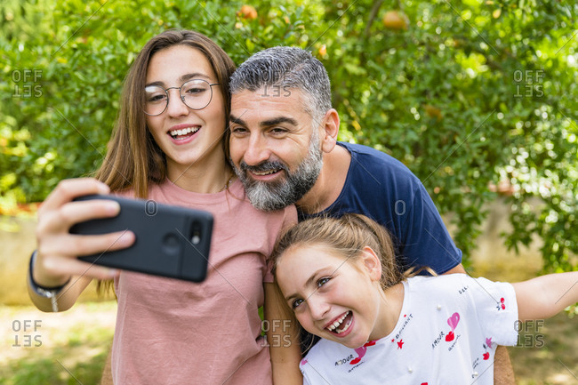 Happy father with two daughters taking selfie in garden