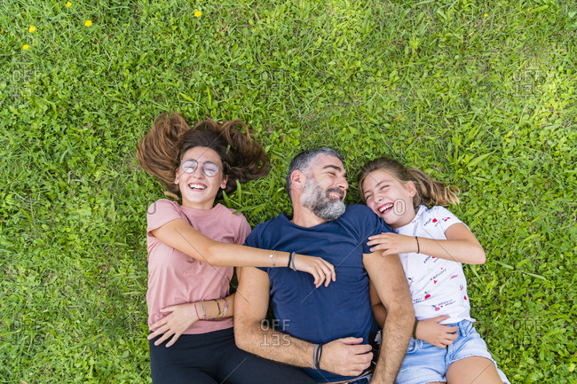 Happy father with two daughters lying on a meadow