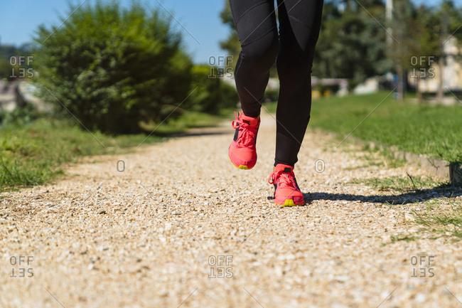 Close-up of woman running on stony path