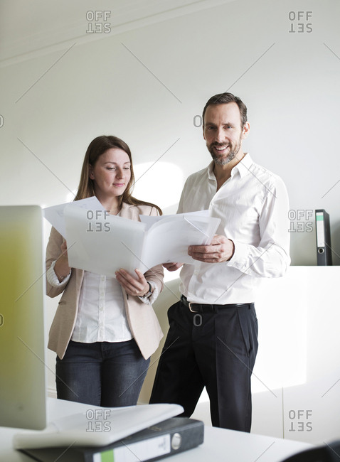 Smiling businessman and employee holding documents in office
