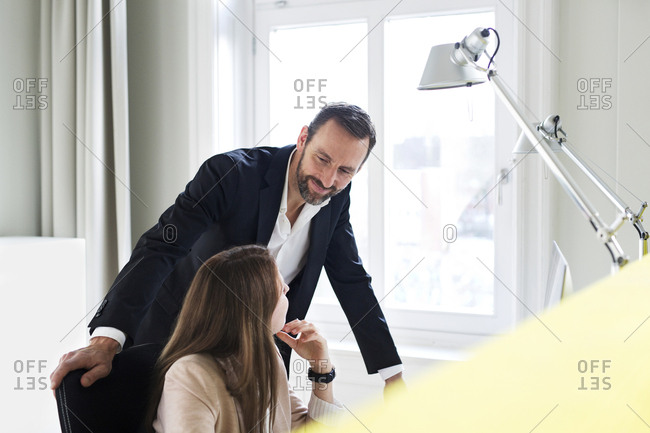 Businessman and employee talking at desk in office