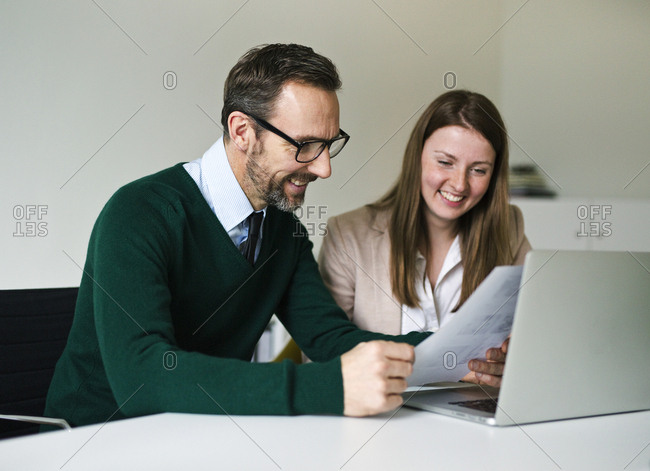 Smiling businessman and employee with laptop and documents working at desk in office