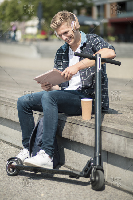 Young man with e-scooter using tablet in the city