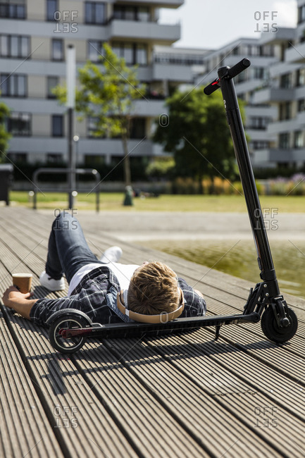 Young man with e-scooter lying on boardwalk