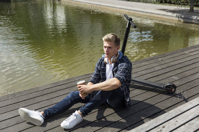 Young man with e-scooter sitting on boardwalk