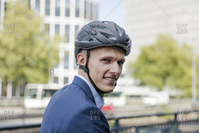 Portrait of smiling young businessman wearing cycling helmet in the city