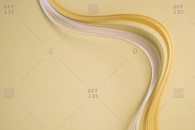 Close-up of curved quilling papers on beige background