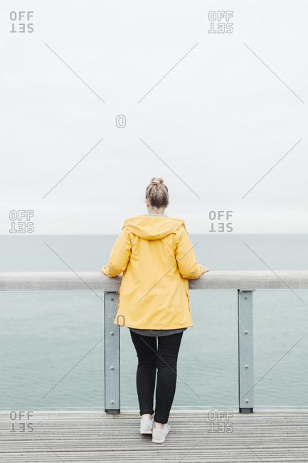 Rear view of young woman wearing yellow rain coat