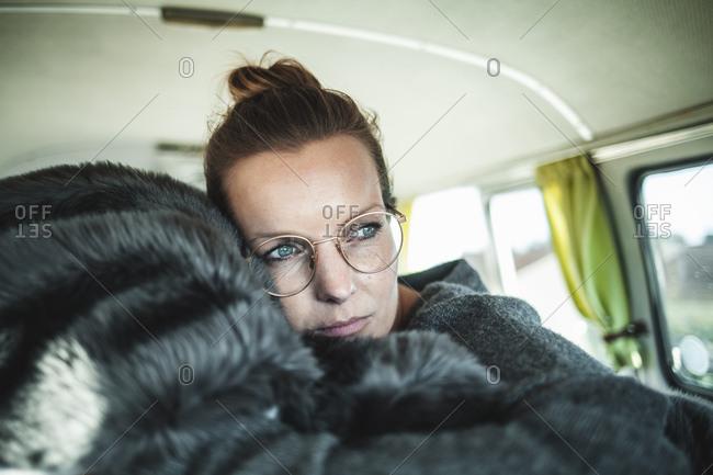 Woman lying on a blanket in a van