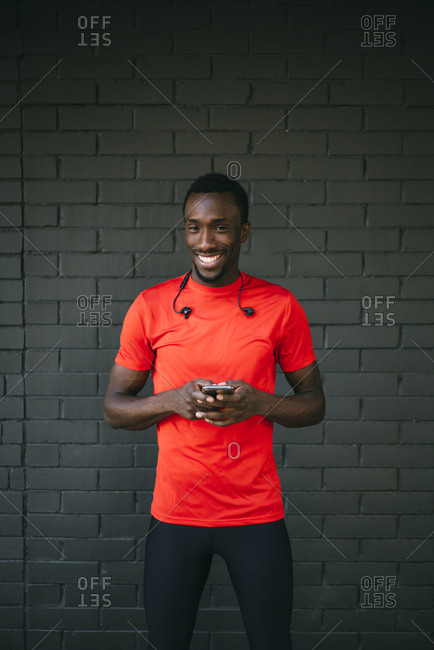 Portrait of a smiling young sportive man standing in front of a brick wall using his smartphone