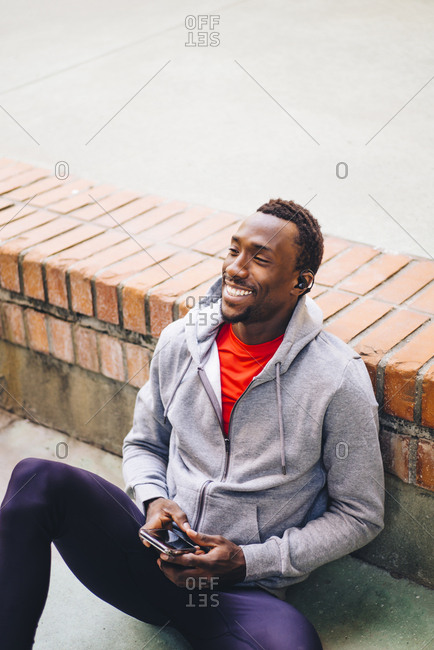 Young sportive man taking a break from workout using his smartphone