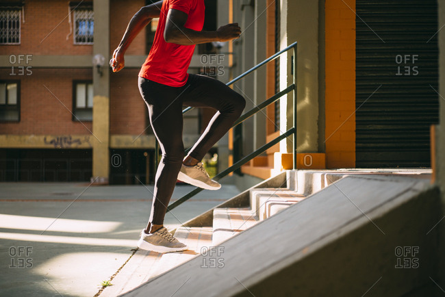 Young sportive man running upstairs on outdoor staircase