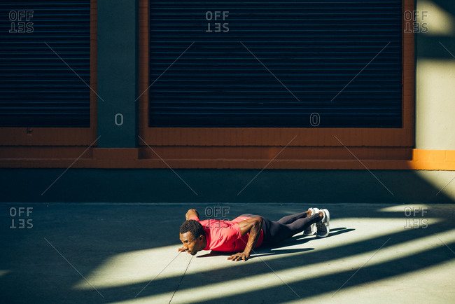 Young sportive man doing pushups outdoors